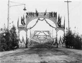 View north across the Rock Bay Bridge, arches erected for the visit of the Duke and Duchess of Co...