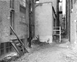 Looking through alley between 536 and 532 Fisgard Street (on left) tenements (on right) towards C...