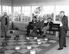 Playing chequers on the giant chequer board in the Chequer House, Beacon Hill Park