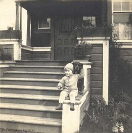 Pat Rochfort on front steps (of family home on Runnymede Ave?) with dog