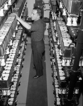 Mr. Basil Kendall in the fire alarm control room.  The control room was located on Fisgard Street...