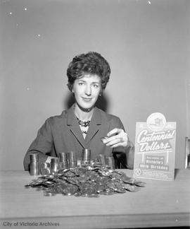 Woman displaying Centennial dollars, a souvenir of Victoria's 100th birthday