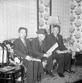 Three Chinese men sitting with presents