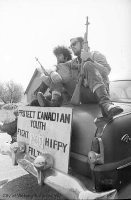 "Two men with guns on car with sign reading ""Protect Canadian youth : fight hippie filth"""