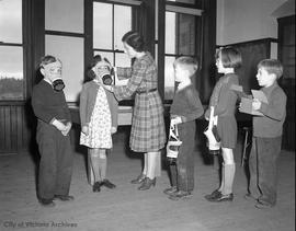 Air raid preparedness, kids fitting gas masks
