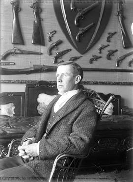 John Barnsley seated in front of displayed weapons