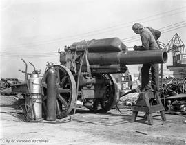 Welder George Taylor cutting up a German field howitzer at Capitol Iron.  The gun was captured at Bourlon Woods in Sept 1918