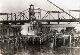 Johnson Street Bridge under construction, driving piles with steam hammer, main trunnion pier