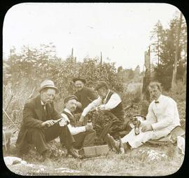 Group of men having a drink on the grass. Percy Lawrie on right in white