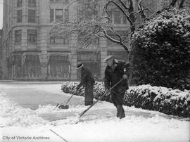 Shovelling snow on Government Street in front of the Empress Hotel