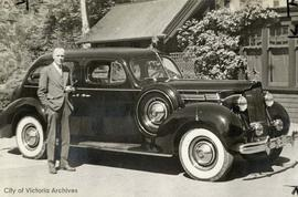 Andrew Mellin with a Packard auto